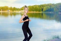 Het jonge meisje oefent yogageschiktheid dichtbij de rivier op een zonnige dag uit royalty-vrije stock fotografie