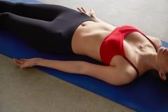 Het jonge meisje ontspannen op een mat Stock Foto's