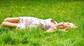 Het jonge meisje ontspannen op een weide Stock Fotografie