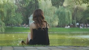 Het jonge meisje ontspannen op groen gras op de bank van de vijver stock videobeelden
