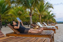 Het jonge meisje ontspant en gebruikt tablet op de strandtoevlucht royalty-vrije stock fotografie