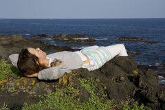 Het jonge Meisje ontspant op klippenrotsen Royalty-vrije Stock Foto's