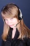 Het jonge meisje in oortelefoons met een microfoon. Royalty-vrije Stock Afbeeldingen