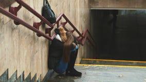 Het jonge meisje op de treden in de metro gedeprimeerde zitting verduistert alleen het gezicht met zijn handsand het schreeuwen D royalty-vrije stock afbeelding