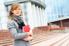 Het jonge meisje op een achtergrond van moderne gebouwen Stock Afbeelding