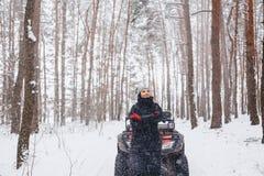 het jonge meisje op een motorfiets berijdt binnen in snow-covered pijnboombos royalty-vrije stock afbeelding