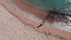 Het jonge meisje op zandig kustmeisje verlaat voetafdrukken op zand Aantrekkelijke vrouw in rode kleding op strand Meisje die lan stock footage