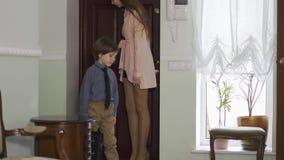 Het jonge meisje opent een deur en komt binnen huis met vermoeide kleine broer die het geven grote schooltas Kinderen als volwass stock videobeelden