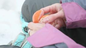 Het jonge meisje pelt mandarin in het de winterbos stock videobeelden