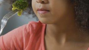 Het jonge meisje probeert broccoli en haat het, kunnen zich de kinderen geen rauwe groenten bevinden stock video