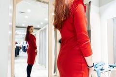 Het jonge meisje probeert op een rode kleding in een boutique van de montageruimte de vrouw koopt kleren in de opslag royalty-vrije stock fotografie