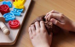 Het jonge meisje ` s overhandigt het kneden deeg Kokende traditionele Pasen-koekjes Pasen-voedselconcept stock fotografie
