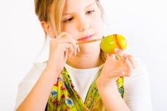 Het jonge meisje schilderen paaseieren Stock Fotografie