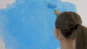 Het jonge meisje schildert het behang met een rol in de ruimte met blauwe verf stock videobeelden