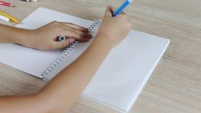 Het jonge meisje schrijft brief terug naar school in document notitieboekje Jonge meisjeszitting door bureaulijst Het witte meisj stock videobeelden
