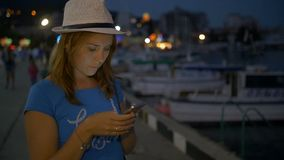 Het jonge meisje schrijft in de boodschapper op mobiele telefoon op achtergrondnachthemel stock videobeelden