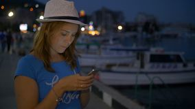 Het jonge meisje schrijft in de boodschapper op mobiele telefoon op achtergrondnachthemel stock video