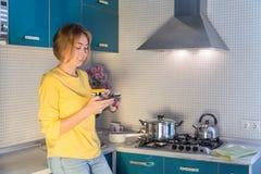 Het jonge meisje schrijft een bericht op de telefoon die zich in de keuken met een mok thee bevinden royalty-vrije stock afbeeldingen