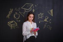 Het jonge meisje, schrijft iets in notitieboekjes, die zich dichtbij een raad met het beeld van de tekens van wetenschap en kenni royalty-vrije stock foto