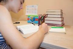 Het jonge Meisje schrijft in notitieboekje tussen boeken Onderwijs en schoolconcept Royalty-vrije Stock Foto's