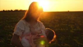 Het jonge meisje schudt weinig baby in glans van het plaatsen van zon De moeder en het kind van het silhouet Jong geitjeslaap in  stock videobeelden