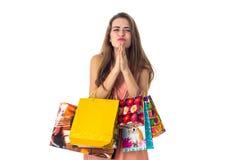 Het jonge meisje sloot haar ogen en houdt zich de vele grote gekleurde pakketten die op witte achtergrond worden geïsoleerd Royalty-vrije Stock Fotografie