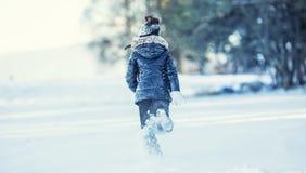 Het jonge meisje speelt met sneeuw Gelukkige het Meisjes Blazende Sneeuw van de schoonheidswinter in ijzig de winterpark of in op stock afbeelding