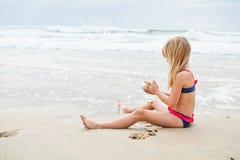 Het jonge meisje spelen bij strand stock foto's