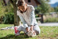 Het jonge meisje spelen met haar huisdierenkonijn stock foto's