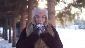 Het jonge meisje spelen met sneeuw in het hout in de winter in openlucht stock video