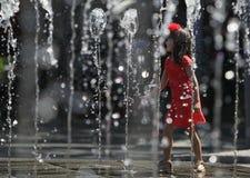 Het jonge meisje spelen met water stock foto's