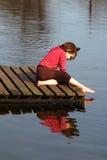 Het jonge meisje spelen naast meer Stock Afbeelding