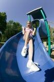 Het jonge meisje spelen op een dia bij het park stock foto's
