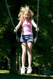 Het jonge meisje spelen op een schommeling die bij het park wordt geplaatst Stock Fotografie