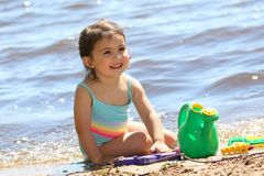 Het jonge meisje spelen op het zand tijdens de zomer Stock Foto's