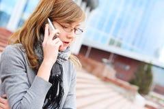 Het jonge meisje spreekt door mobiele telefoon. Zaken Royalty-vrije Stock Afbeeldingen