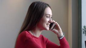 Het jonge meisje spreekt telefonisch stock video