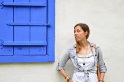 Het jonge meisje stellen door de blauwe vensterblinden royalty-vrije stock afbeelding