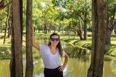 Het jonge meisje stellen op de kust van een rivier stock foto's