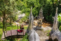 Het jonge meisje stelt bij een Boeddhistische tempel Wat in Chiang Mai stock fotografie