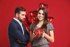 Het jonge meisje stelt een gift en ballons aan de haar boze knappe mens voor Royalty-vrije Stock Afbeeldingen