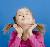 Het jonge meisje toont twee vlechten royalty-vrije stock fotografie