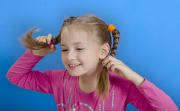 Het jonge meisje toont twee vlechten royalty-vrije stock afbeelding