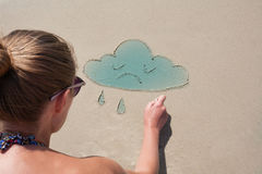 Het jonge meisje trekt op het zand op het strand een wolk Weervoorspelling, stemming Bewolkt, bewolking Royalty-vrije Stock Afbeelding