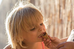 Het jonge meisje van het blondekind eet een chocoladeroomijs van haar mum` s hand Warm zonsonderganglicht De reisvakantie van de  Stock Afbeelding