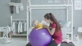 Het jonge meisje van de moeder slingerende baby op fitball thuis stock video