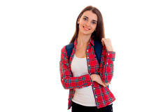 Het jonge meisje van de schoonheids donkerbruine student met rugzak bij haar schouders glimlachen op camera geïsoleerd op witte a Stock Foto's