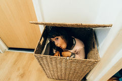 Het jonge meisje verbergen in mand Stock Foto