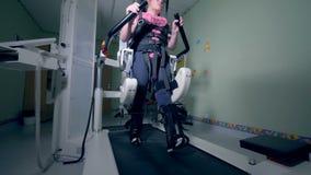 Het jonge meisje versterkt haar lager lichaam op een spoorsimulator stock videobeelden