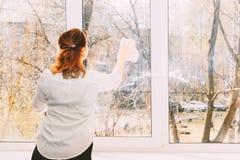 Het jonge meisje wast en maakt zorgvuldig een venster schoon royalty-vrije stock fotografie